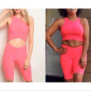 Neon pink crop top and bike shorts set.